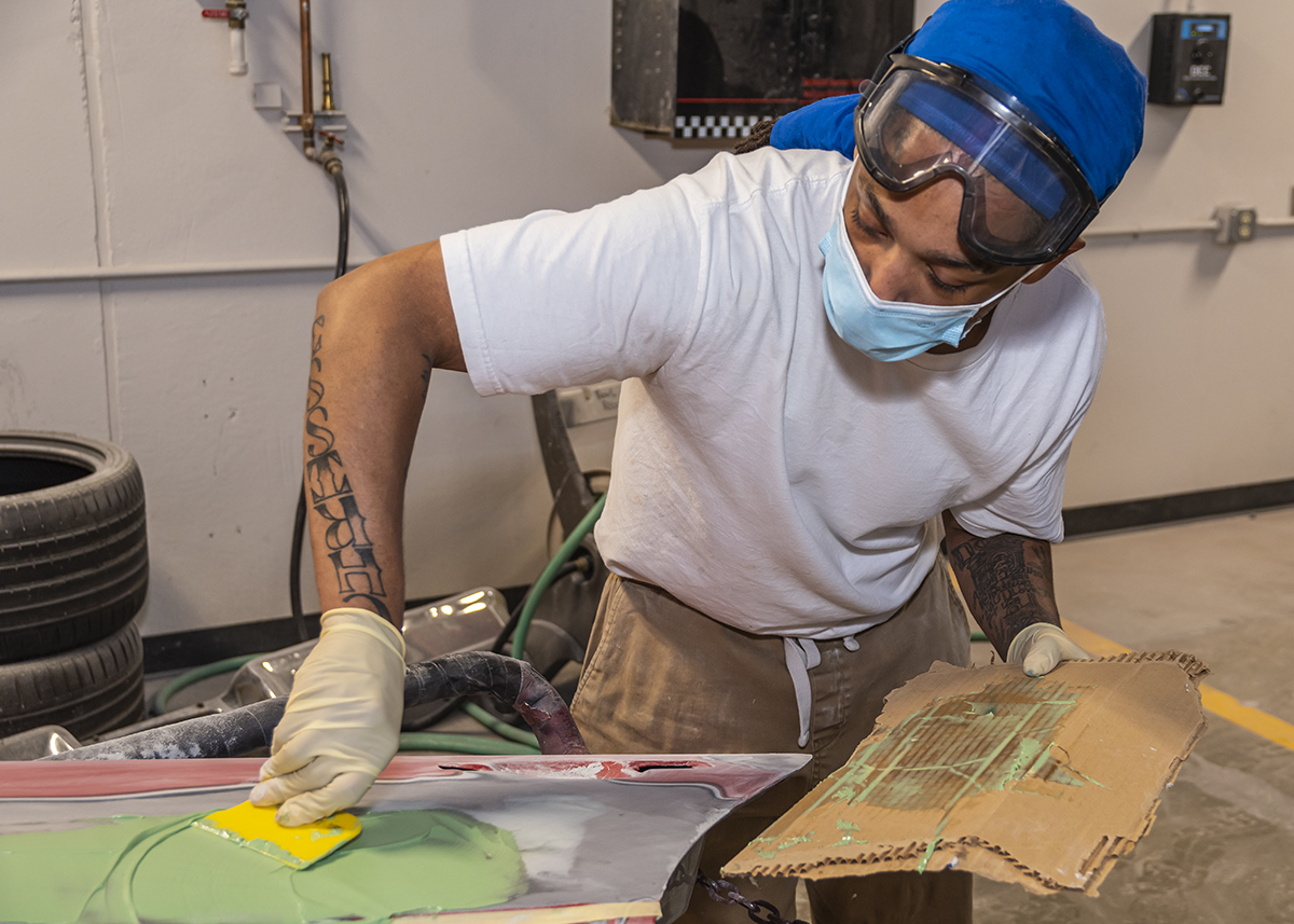 Masked student gains valuable skills and protection in autobody lab