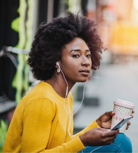 Black woman holding cell phone and coffee with earbuds.